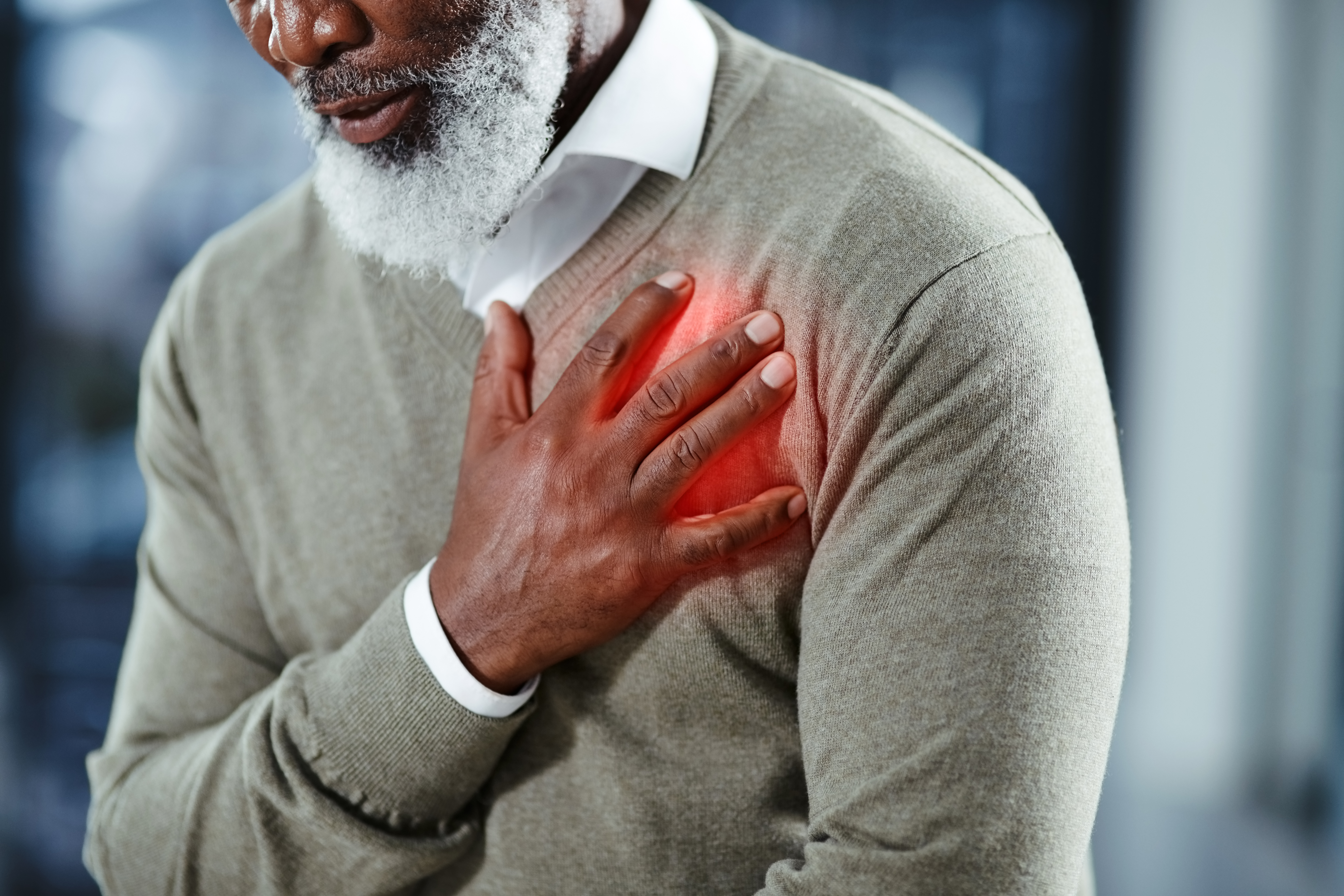 older man hand on heart in pain
