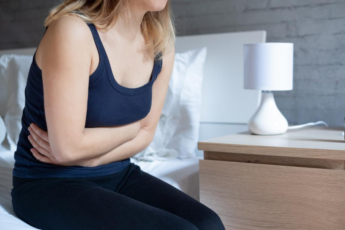 Woman holding her stomach due to nausea in the morning