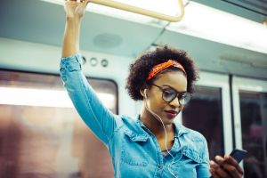 A woman listens to music on the subway, using earbuds.