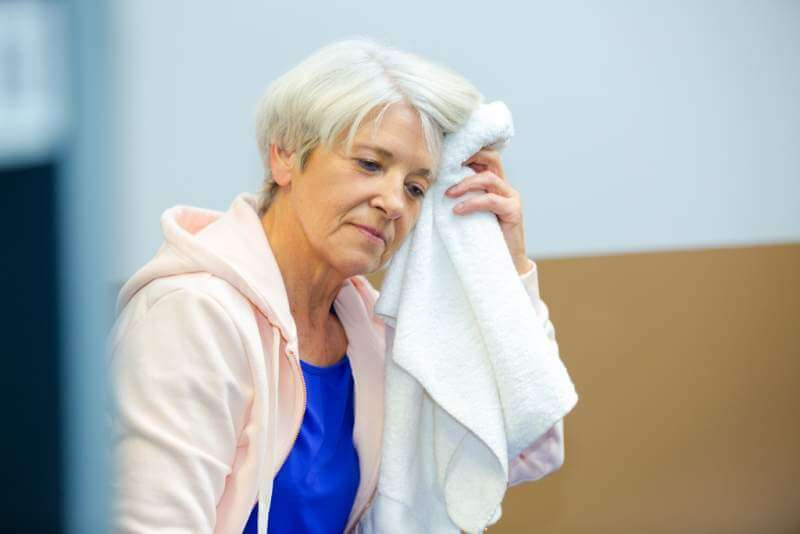 senior-woman-mopping-brow-with-towel-after