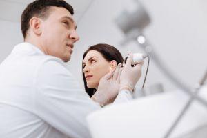 A woman receives a hearing exam.