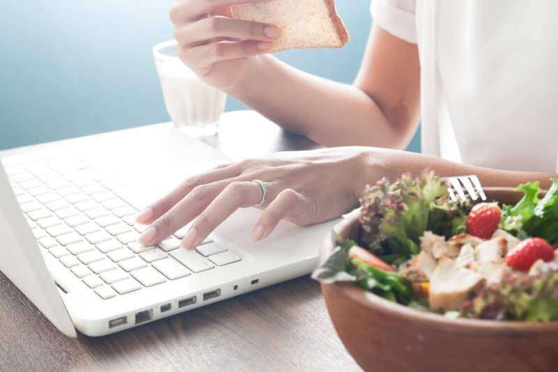 Woman's hand using laptop computer and eating sliced bread with salad bowl in foreground
