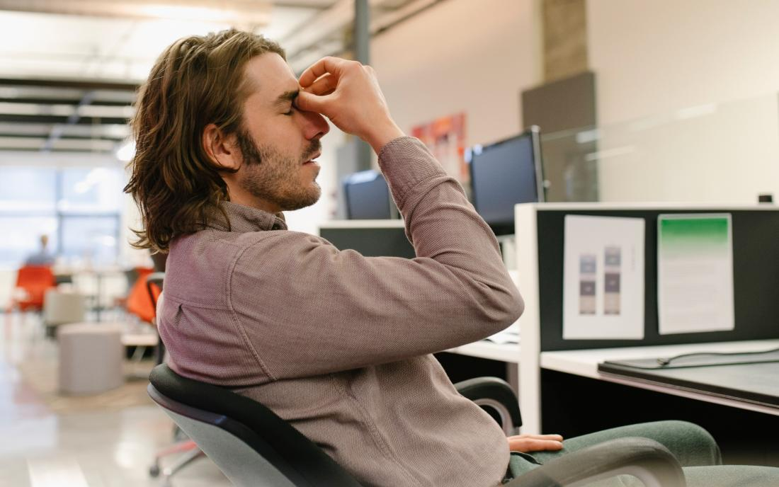 a man experiencing positional headache whilst sat on a chair as at a desk.