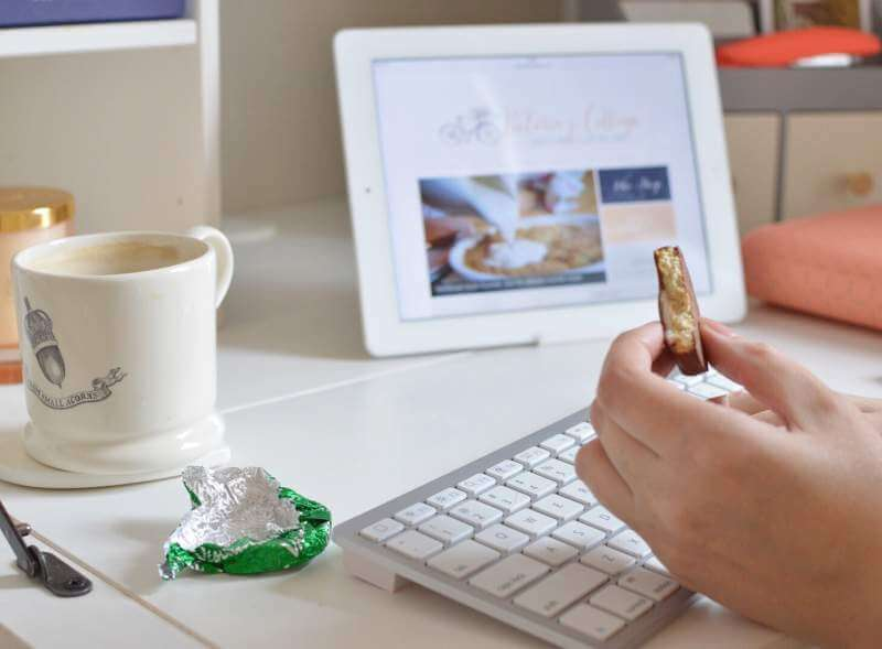 a-womans-hand-holding-a-half-eaten-biscuit-at-a-desk-filled-with-a-computer-and-stationery