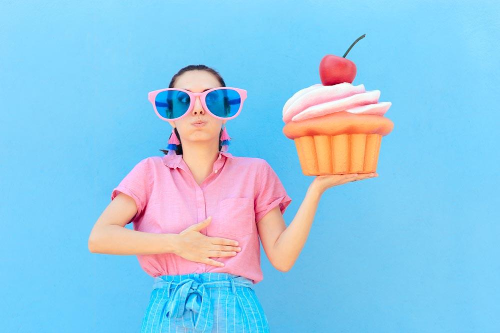 bad-habits-eating-too-much-sugar-woman-holding-cupcake.jpg