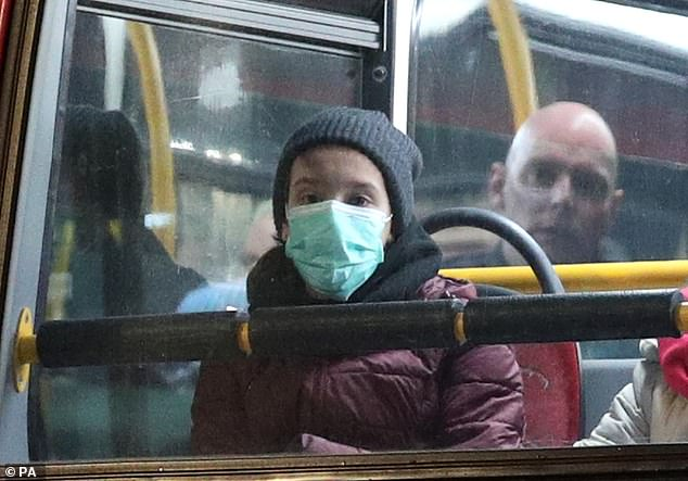 The latest case is the first time a patient has caught the infection on British soil, marking a 'new chapter' in the country's spiralling health crisis. Pictured: A bus passenger wears a protective mask