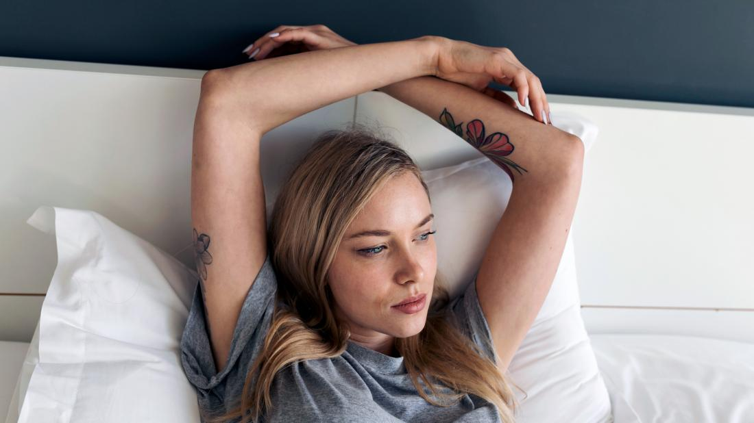 a woman lying in bed and wondering why she has so much discharge
