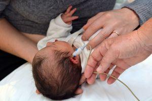 A newborn receives a hearing screening.