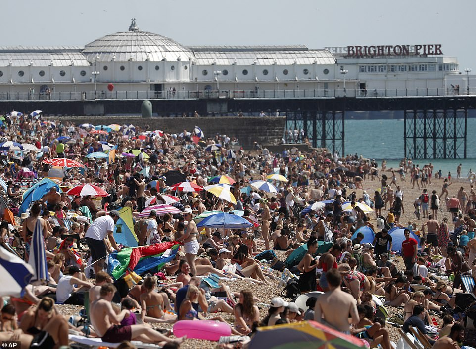 Beachgoers enjoy the sunshine and sea at a packed Brighton beach in East Sussex this afternoon